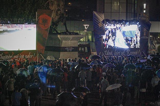 Dy ekrane të mëdha u vendosën në të dy anët e përmendores së Skenderbeut në qendër të Prishtinës për t'u ofruar mundësi tifozëve ta përcjellin edhe ndeshjen e Kosovës edhe atë të Shqipërisë. (Foto: Fikret Ahmeti / K2.0)