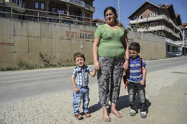 Selvie Haliti dhe djemtë e saj presin autobusin për të shkuar në shkollë në Fushën e Pajtimit, një nga dy lagjet e Prishtinës që ofrojnë strehim social për familjet, si ajo e Halitit.