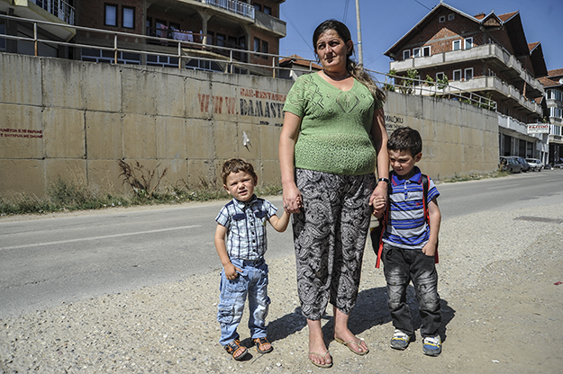 Selvie Haliti and her sons wait for the bus to school in the Field of Reconciliation, one of two neighborhoods in Prishtina providing social housing to families like Haliti's.