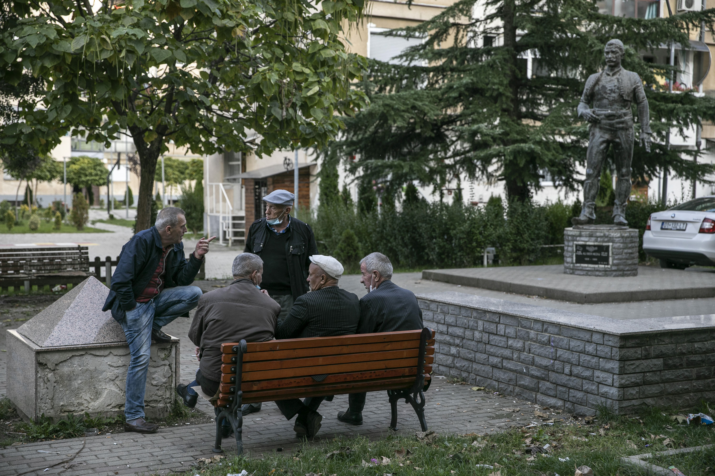 Elderly men chatting at a square in Gjakova.